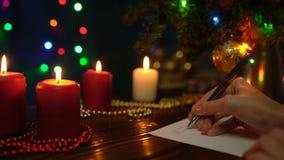 Девушка подписывает поздравительные открытки рождества на предпосылке рождественской елки, покрашенных светов и свечей акции видеоматериалы