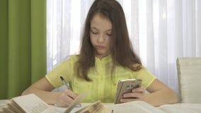 Девушка подростка делает домашнюю работу с видео отснятого видеоматериала запаса smartphone видеоматериал