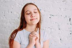 Девушка подростка красивого очаровательного redhead усмехаясь закрывая ее глаза и делая изолированное желание на белой кирпичной  стоковые фотографии rf