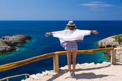 Девушка подростка наслаждается ветром, солнечностью и взглядом, на крае высокой скалы над голубым морем Греции стоковые фотографии rf