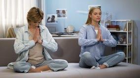 Девушка подростка при мать делая жест во время тренировок, сработанность йоги namaste стоковое фото rf