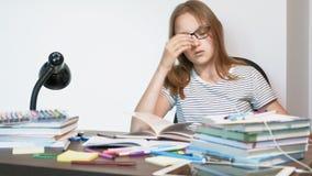 Девушка подростка со стеклами сидит на столе школы r акции видеоматериалы