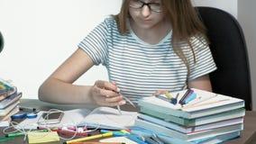 Девушка подростка со стеклами сидит на столе школы r сток-видео