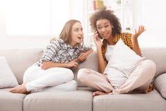 Девушка подслушивая ее мобильный телефон подруги для того чтобы поговорить Стоковые Изображения RF