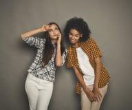 Девушка подслушивая ее мобильный телефон подруги для того чтобы поговорить Стоковое Фото