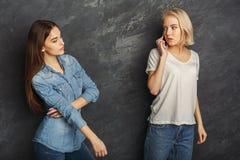 Девушка подслушивая ее мобильный телефон подруги для того чтобы поговорить Стоковые Фото