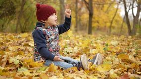 Девушка показывает ее палец в небе в парке в осени видеоматериал