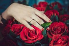 Девушка показывает ее подарок обручального кольца Звените с диамантом на предпосылке букета красных роз розы кольца предложения з Стоковое Изображение RF