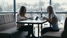 Девушка показывает к подруге что-то на сенсорной панели сток-видео