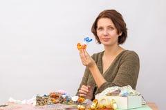 Девушка показывает домодельный кран на таблице с needlework Стоковое Фото
