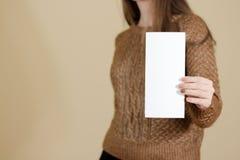Девушка показывая пустой белый буклет брошюры рогульки Листовка присутствующая Стоковое Изображение