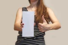 Девушка показывая пустой белый буклет брошюры рогульки Листовка присутствующая Стоковые Фотографии RF