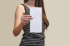 Девушка показывая пустой белый буклет брошюры рогульки Листовка присутствующая Стоковая Фотография RF