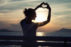 Девушка показывая сердце на небе стоковое фото rf