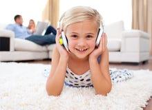 девушка пола слушая меньшее лежа нот Стоковая Фотография RF