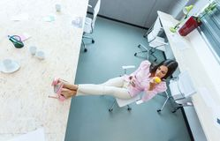 Девушка положила ее ноги на стол в офис стоковые изображения