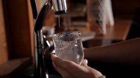 Девушка получая стекло воды от крана в раковине и выпивать акции видеоматериалы