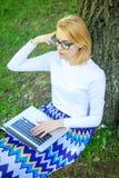 Девушка пользуется виртуальным образованием Девушка сидит трава с тетрадью Сохраньте ваше время с виртуальным образованием Студен стоковое изображение rf