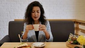 Девушка портрета в синем пиджаке, имеющ завтрак сидя на серой софе, она принимает глоточек свежего кофе, кладет чашку на tabl акции видеоматериалы