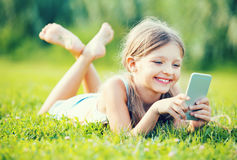 Девушка портрета лежа в парке и играя с мобильным телефоном Стоковые Изображения