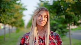 Девушка портрета милая белокурая с красивыми длинными волосами в красном положении рубашки шотландки милом усмехаясь на переулке сток-видео