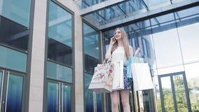 Девушка портрета образа жизни молодая белокурая, с хозяйственными сумками идя вне от магазина видеоматериал