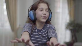 Девушка портрета счастливая с наушниками танцуя и слушая к музыке видеоматериал