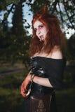 Девушка портрета с красными волосами и кровопролитным вампиром стороны, душегубом, психопат, темой хеллоуина, кровопролитной женщ Стоковое фото RF