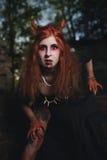 Девушка портрета с красными волосами и кровопролитным вампиром стороны, душегубом, психопат, темой хеллоуина, кровопролитной женщ Стоковые Изображения RF