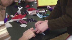 Девушка порции женщины с цветком на голове делает мягкую ручной работы игрушку на таблице празднество творение акции видеоматериалы