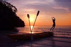 Девушка поскакала от каяка на пляже на заходе солнца Стоковое фото RF