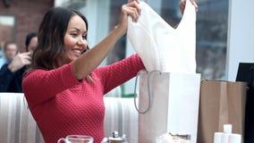 Девушка после ходя по магазинам сидеть в кафе и фотографировать внутренность хозяйственных сумок и всего она купила Стоковые Фото