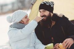 Девушка подает мальчик с зефиром на барбекю зимы Стоковые Фотографии RF