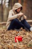 Девушка подготавливает еду на газовой горелке стоковое фото rf