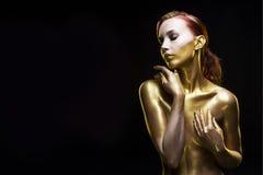 Девушка подкрашиванная в золоте на черной предпосылке Стоковые Изображения