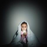Девушка под крышками с электрофонарем Стоковая Фотография RF