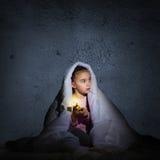 Девушка под крышками с электрофонарем Стоковая Фотография