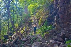 Девушка поднимает через красивую заросшую лесом скалу, серии растительности и скалы стоковое фото rf