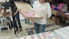 Девушка положила красочные донуты на таблицу от коробки в торговый центр справедливо люди сток-видео