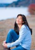 Девушка подростка в голубой рубашке и джинсы сидя вдоль скалистого озера подпирают Стоковая Фотография RF