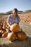 Девушка подростка в рубашке шотландки выбирая тыквы Стоковое Изображение