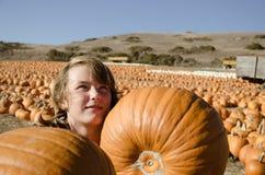 Девушка подростка в рубашке шотландки выбирая тыквы Стоковые Изображения