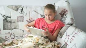 Девушка подростка лежа на кровати с цифровой таблеткой акции видеоматериалы