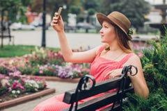 Девушка подростка использует телефон в парке Стоковая Фотография RF
