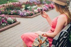 Девушка подростка использует телефон в парке Стоковое Фото