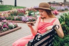 Девушка подростка использует телефон в парке Стоковая Фотография