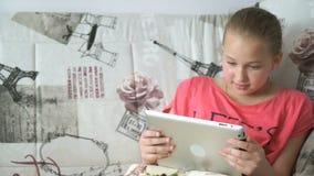 Девушка подростка использует цифровую таблетку на кровати сток-видео