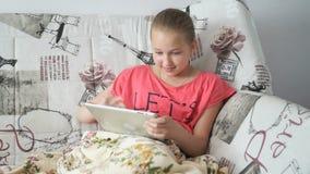 Девушка подростка использует цифровую таблетку на кровати акции видеоматериалы