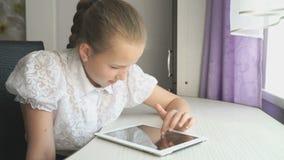 Девушка подростка использует цифровую таблетку на столе видеоматериал