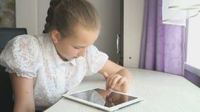 Девушка подростка использует цифровую таблетку на столе сток-видео